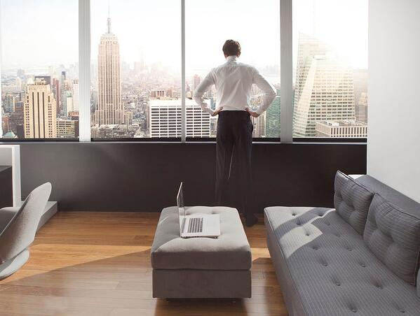 अपने लक्जरी अपार्टमेंट में एक जवान आदमी न्यूयॉर्क क्षितिज पर बाहर देख
