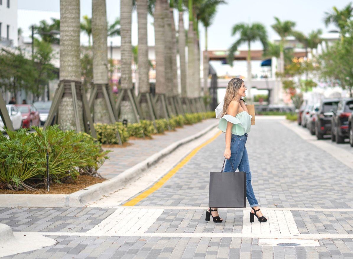 महिला एक शॉपिंग बैग पकड़े और कोरल Gables में सड़क पार